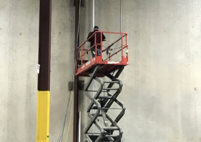 Installing conduit off a scissor lift.